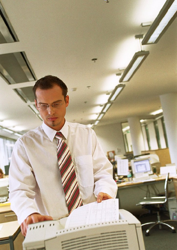 Businessman using copy machine : Stock Photo