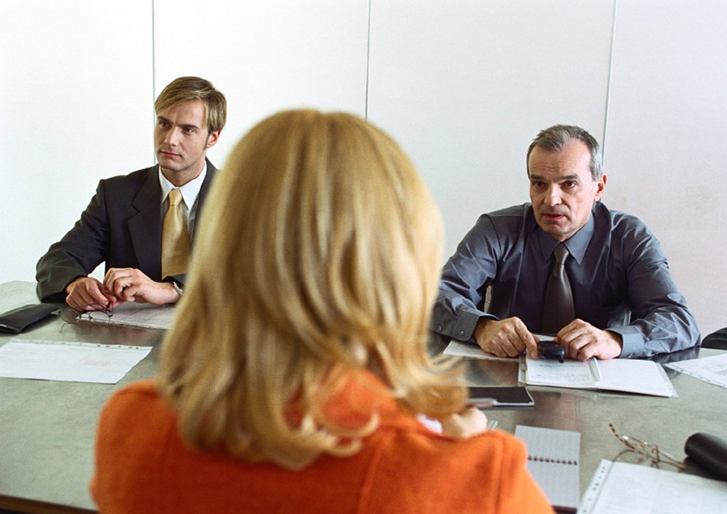 Stock Photo: 1569R-202054 Businessmen and businesswoman sitting at table, woman´s back to camera