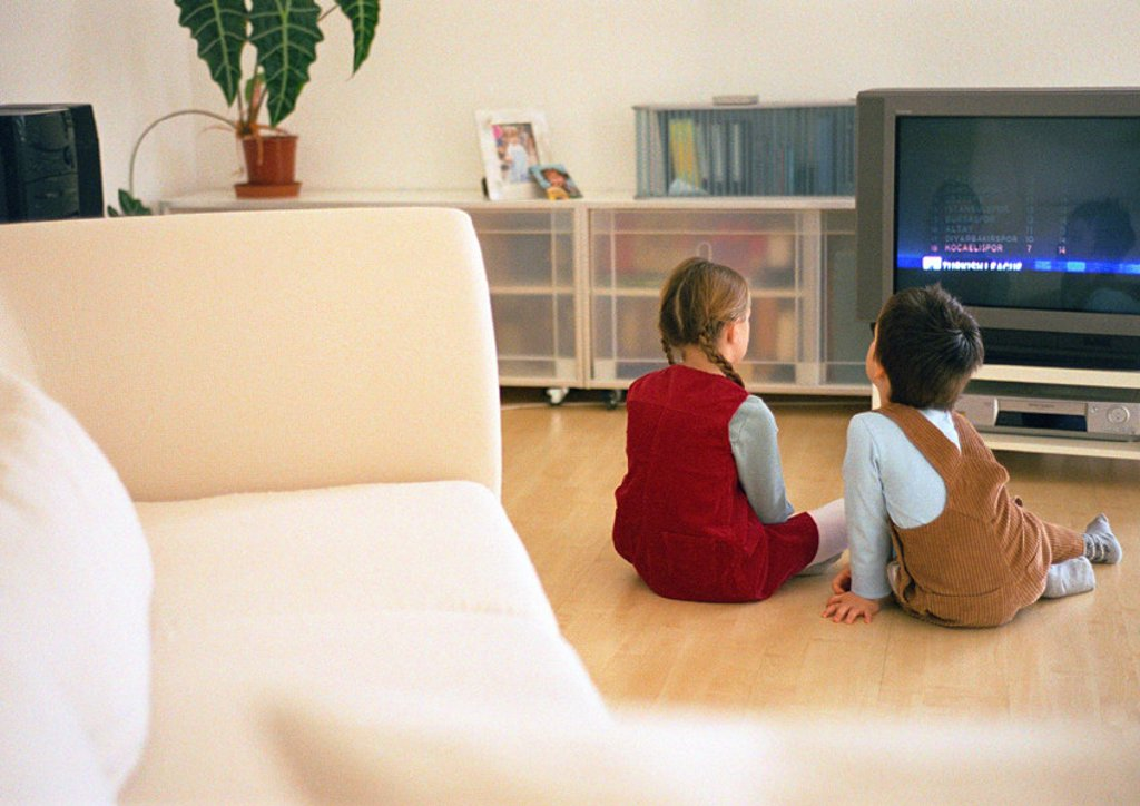 Lttle boy and girl sitting together on parquet floor looking at tv, rear view : Stock Photo
