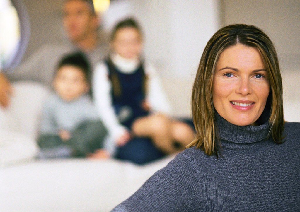 Family, mother in foreground, husband and two children blurred in background, close up : Stock Photo