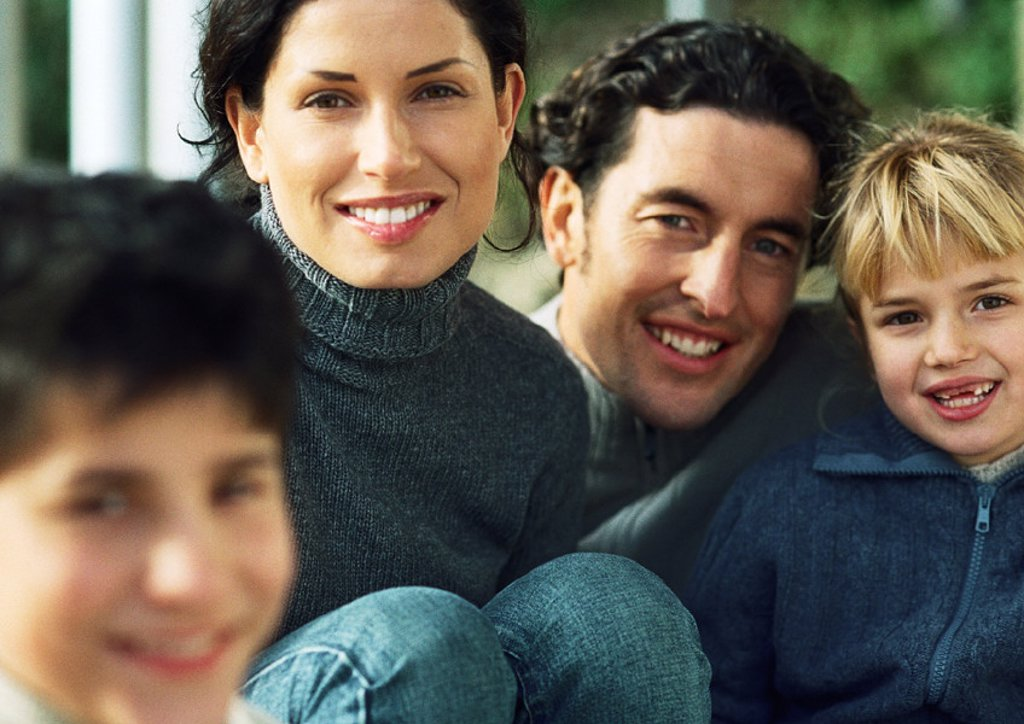 Stock Photo: 1569R-203040 Adult man and woman with little girl, smiling, in background, little boy blurred in foreground