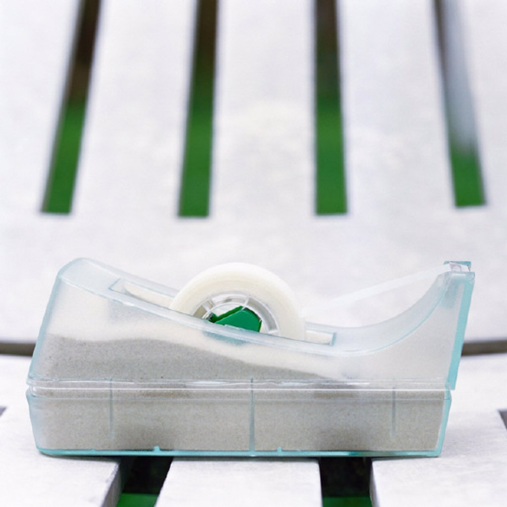 Stock Photo: 1569R-208004 Adhesive tape dispenser on plastic lounge chair, close-up