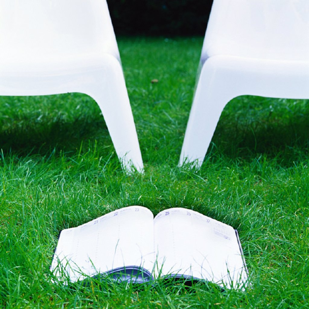 Book and two plastic chairs on grass : Stock Photo