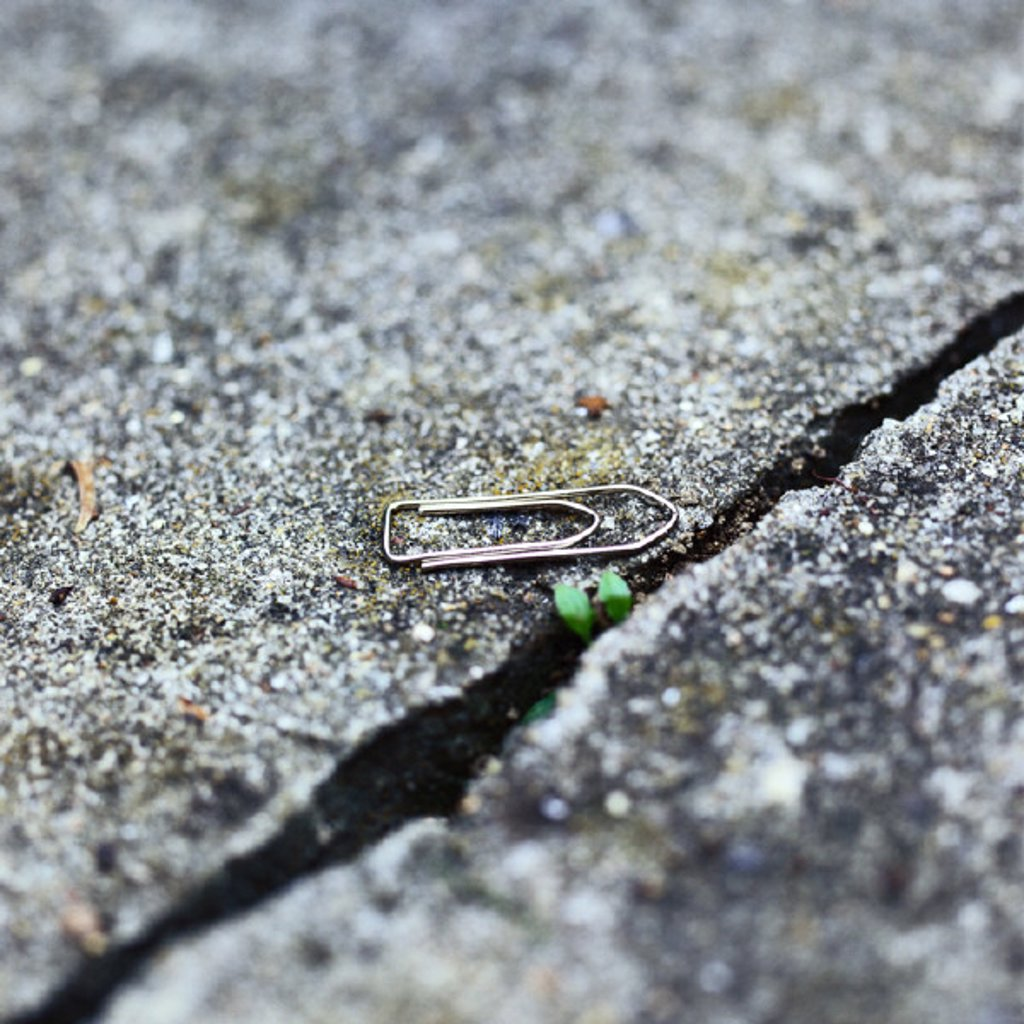 Paper clip on ground near crack : Stock Photo