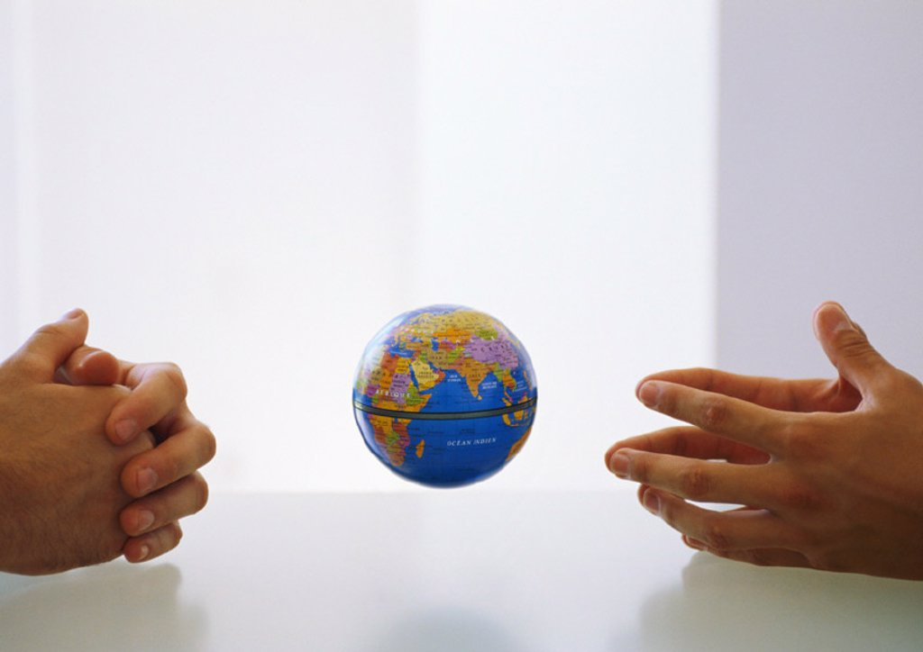 Globe between two pairs of clasped hands : Stock Photo