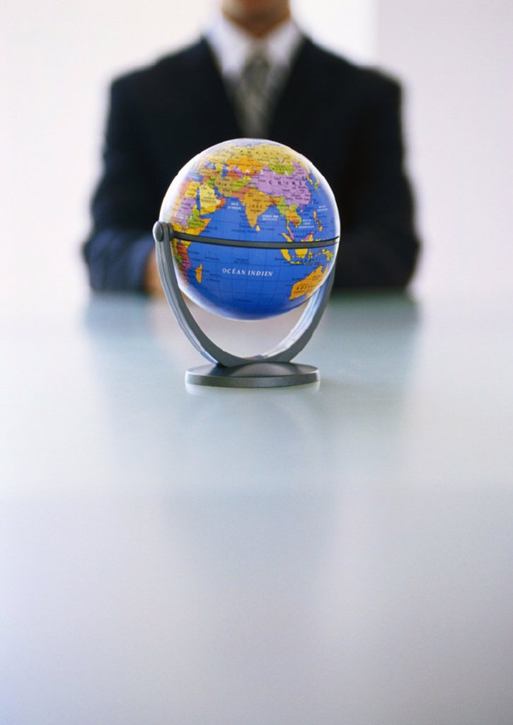 Globe, businessman in background : Stock Photo