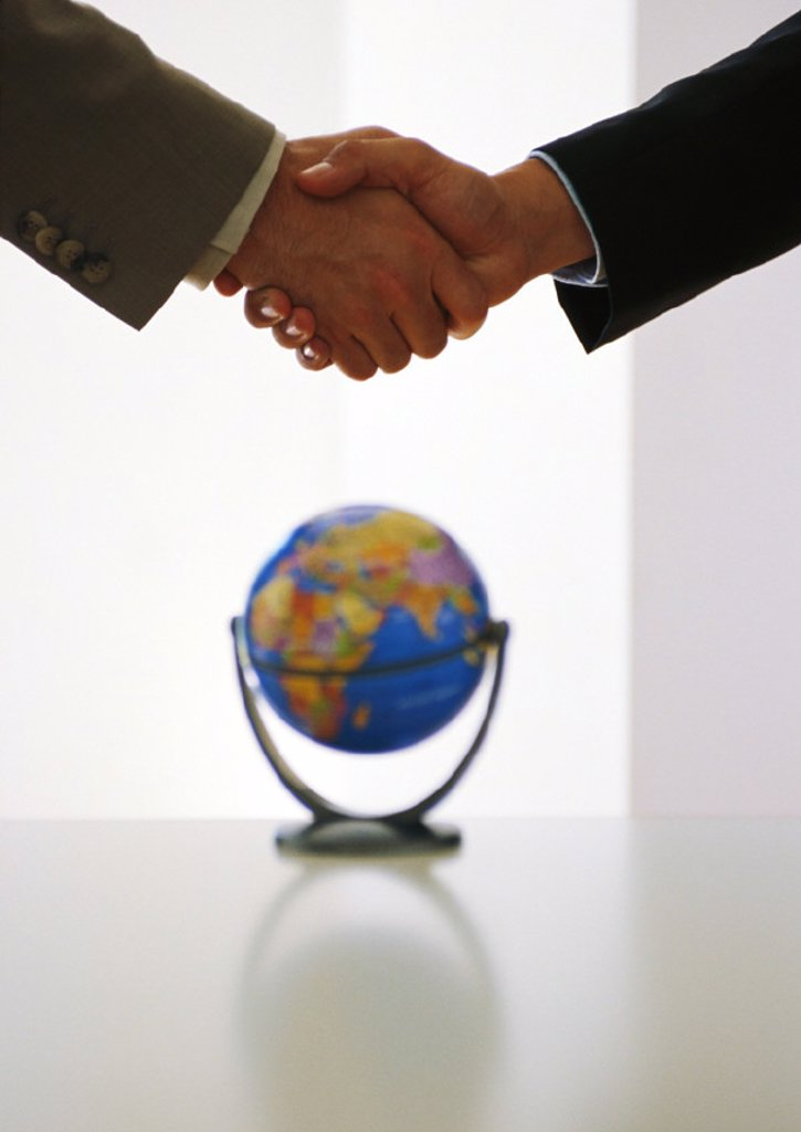 Two businessmen shaking hands above globe : Stock Photo