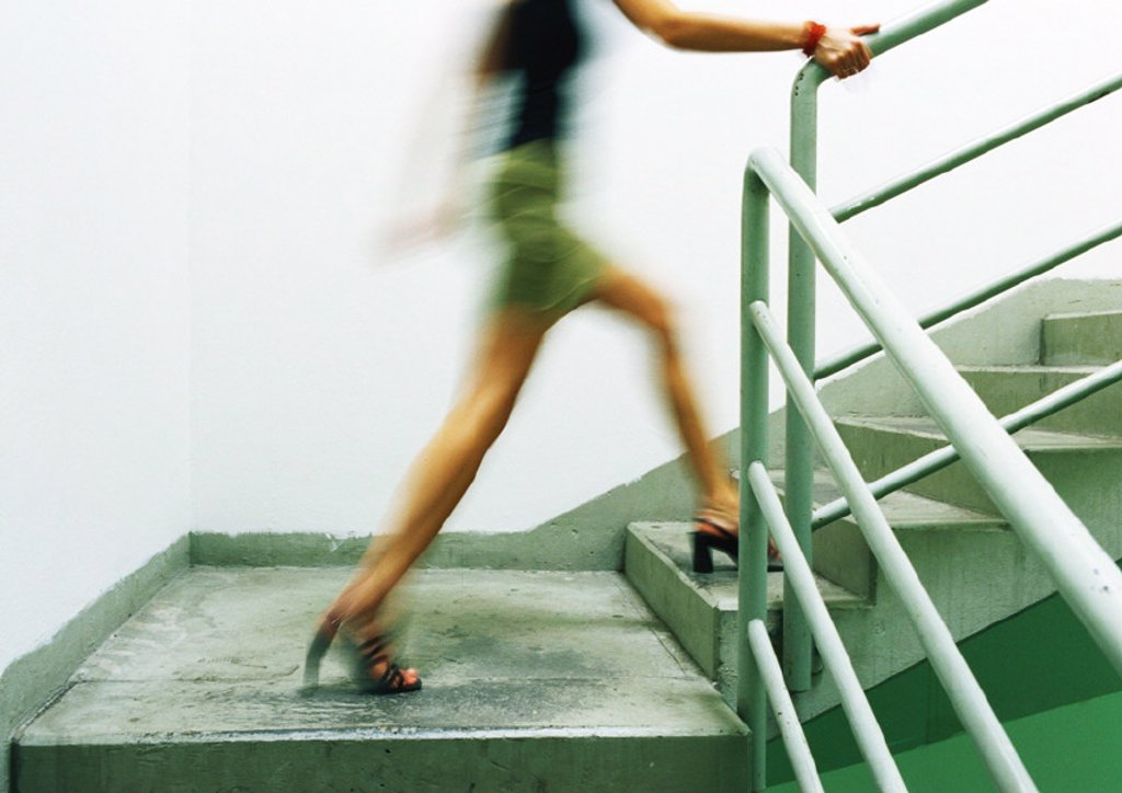 Woman walking up stairs, blurred : Stock Photo