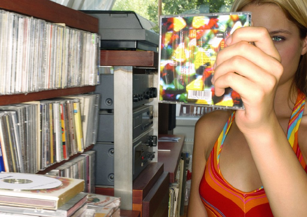 Young woman looking at CD collection : Stock Photo
