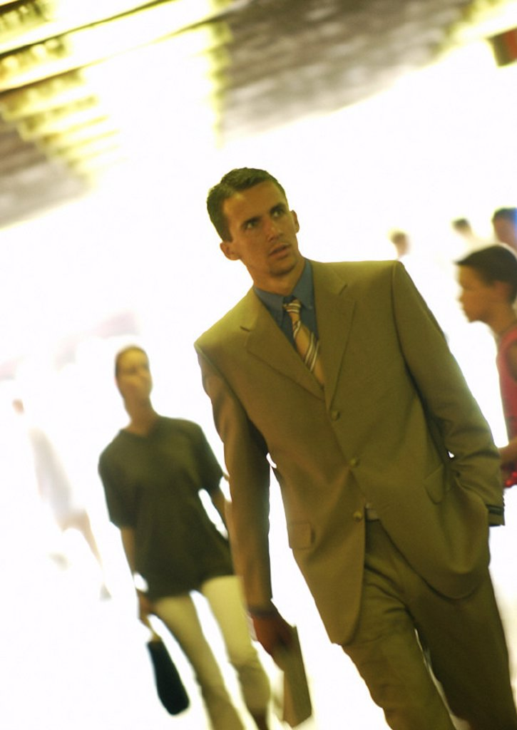 Businessman walking among crowd : Stock Photo