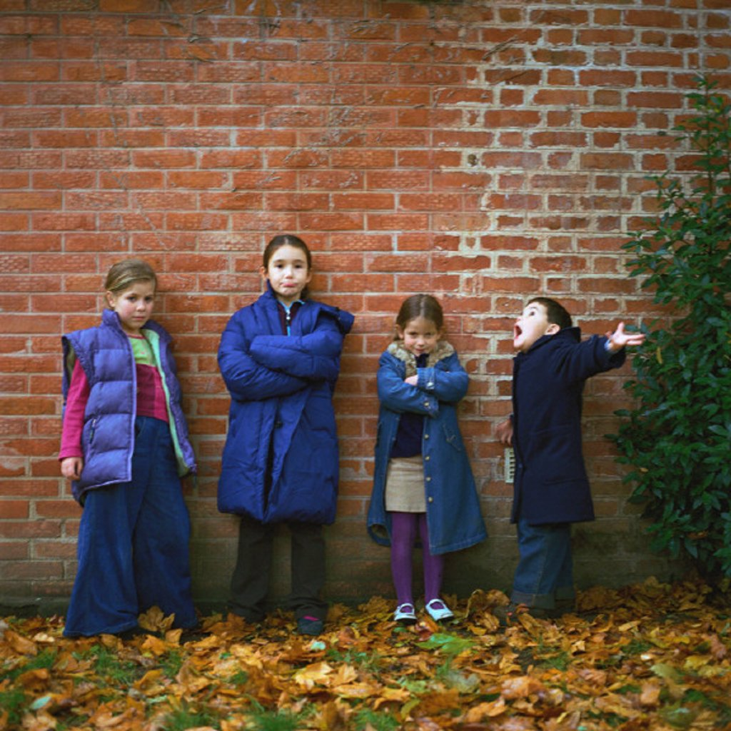 Four children wearing coats in front of brick wall, full length : Stock Photo