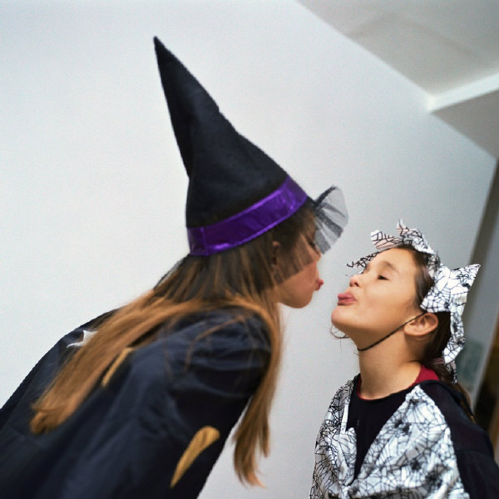 Stock Photo: 1569R-222037 Two girls wearing costumes, sticking out tongues at each other