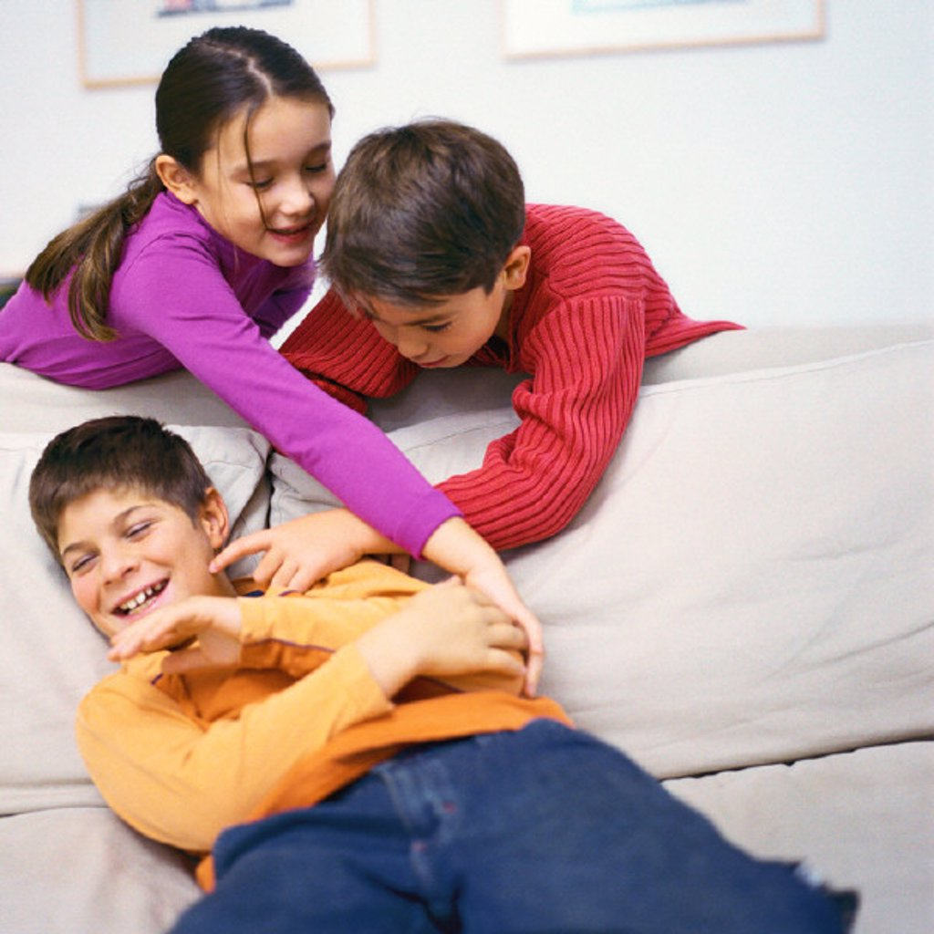 Boy and girl leaning over sofa, tickling second boy on sofa : Stock Photo