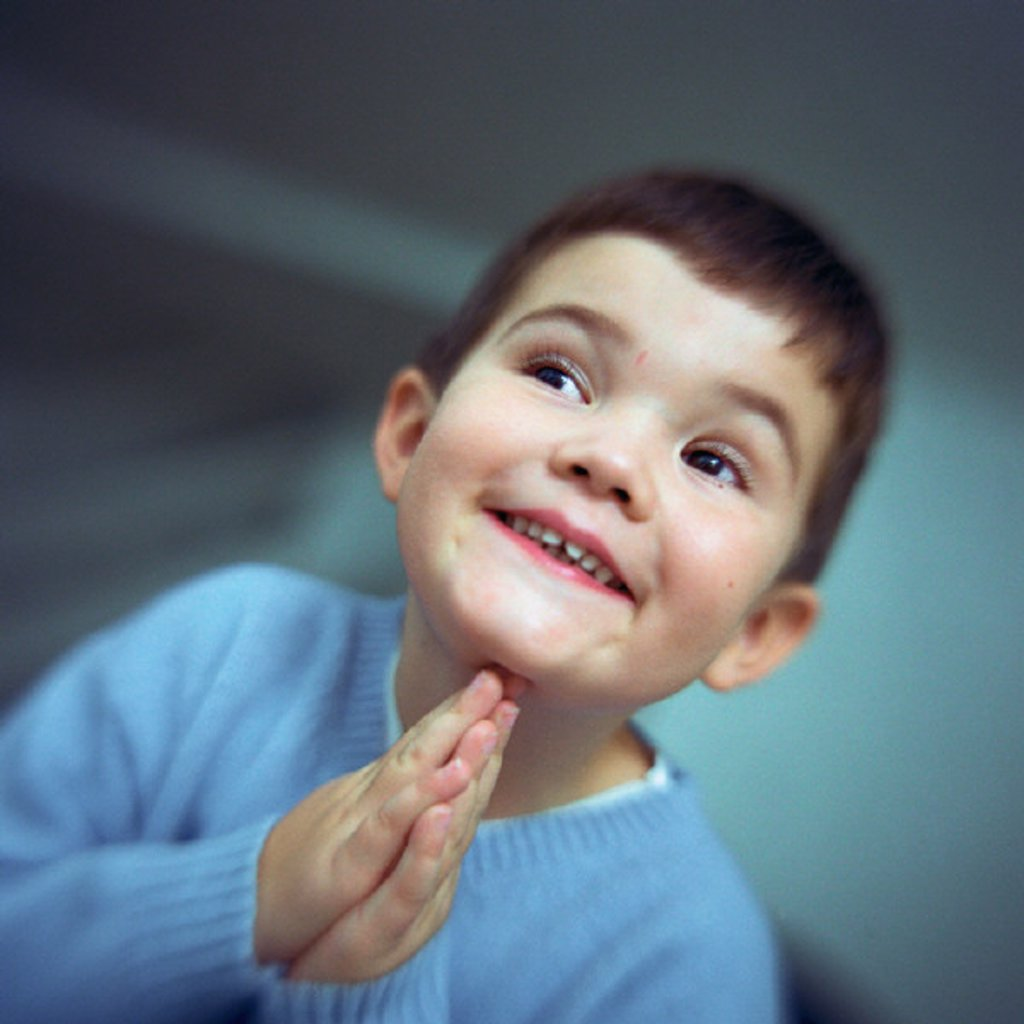 Boy smiling, looking to the side with hands together, portrait : Stock Photo
