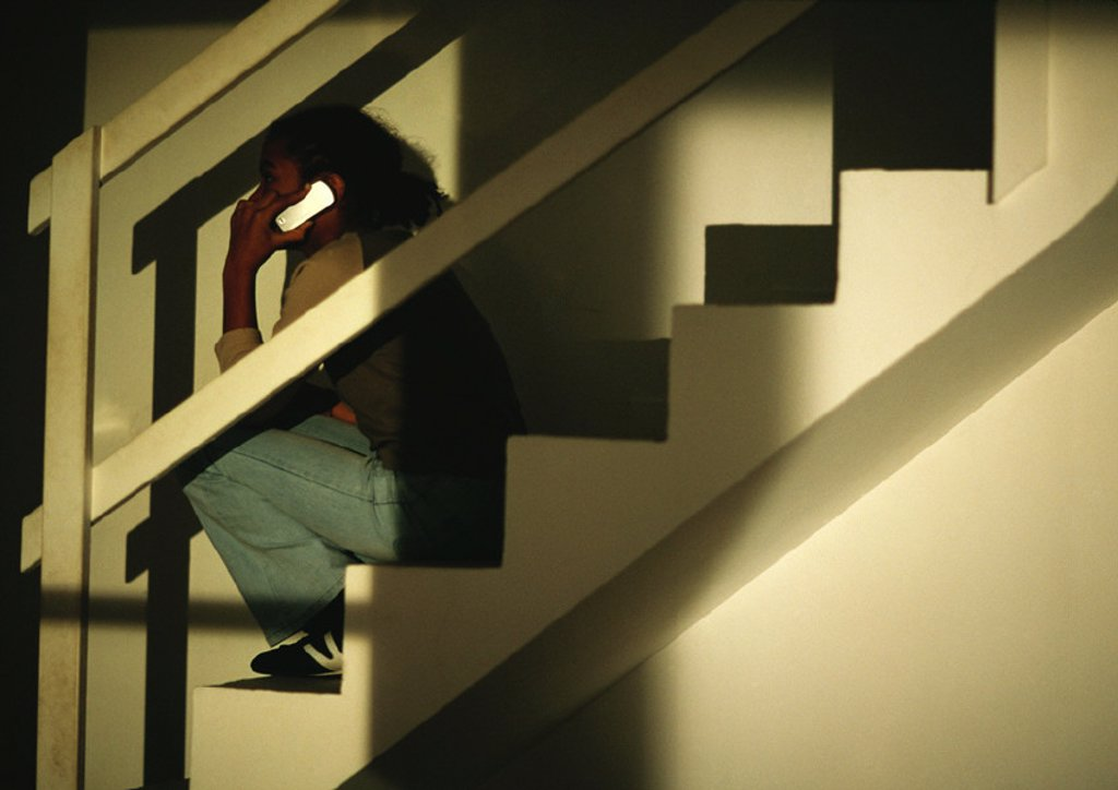 Young boy sitting on stairs talking on phone : Stock Photo