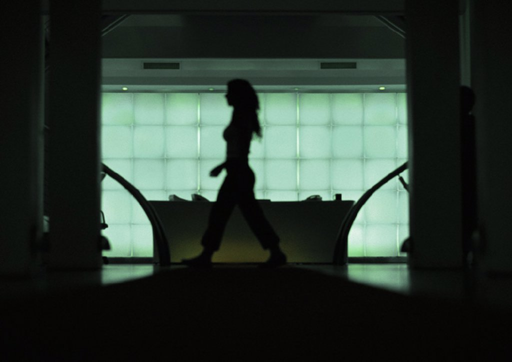 Woman walking in front of desk, silhouette, view through doorway : Stock Photo