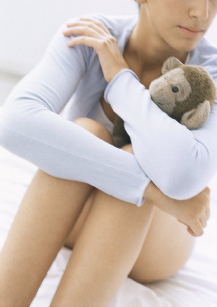 Woman sitting barelegged with knees up, hugging stuffed monkey, partial view, close-up : Stock Photo