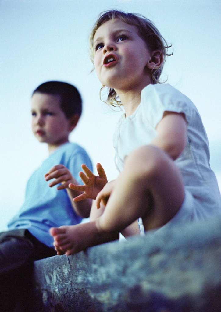 Two children sitting outdoors, low angle view : Stock Photo