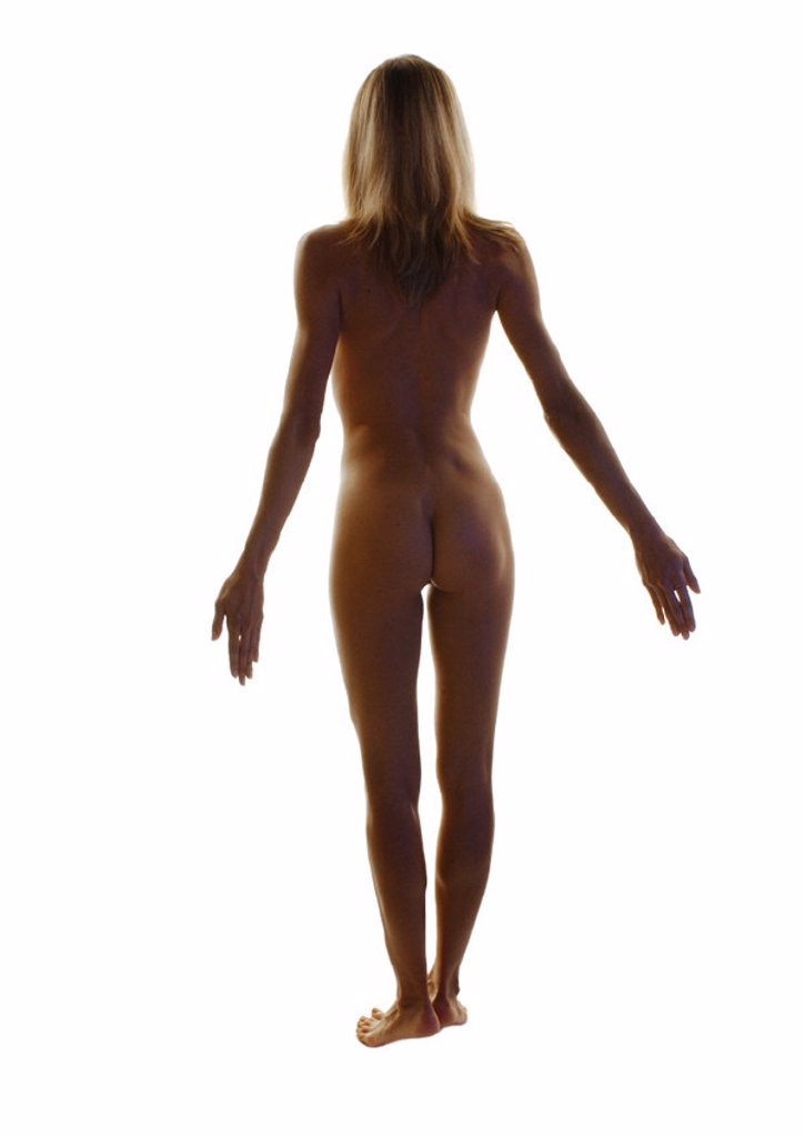 Nude woman standing with arms back, full length, rear view : Stock Photo