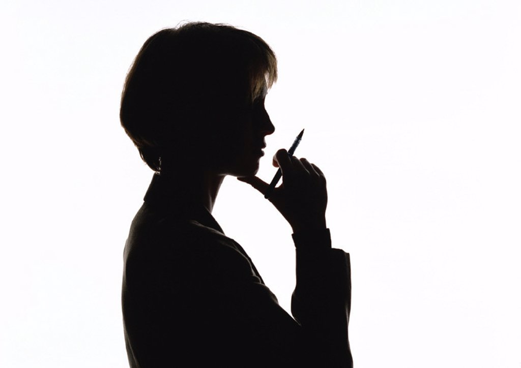Stock Photo: 1569R-25020 Woman holding pen near mouth, silhouette