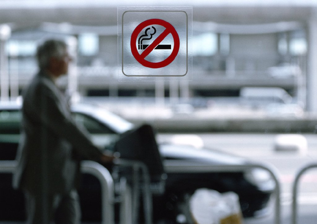 Man standing outside, no smoking sign on window in foreground : Stock Photo