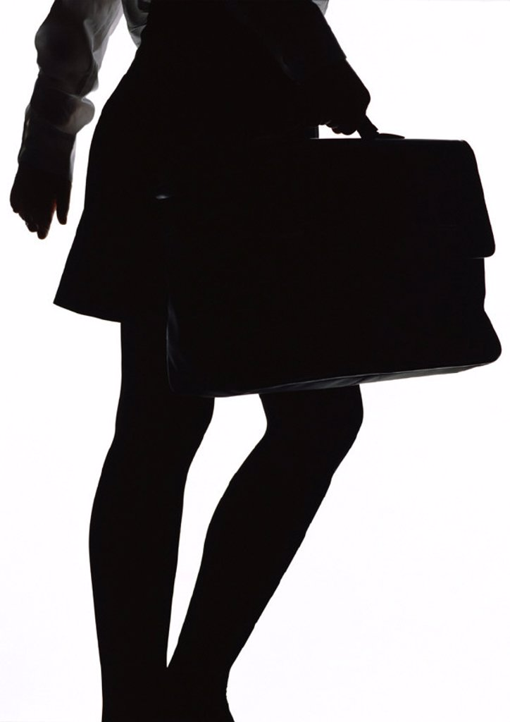 Stock Photo: 1569R-25117 Woman walking with briefcase, silhouette