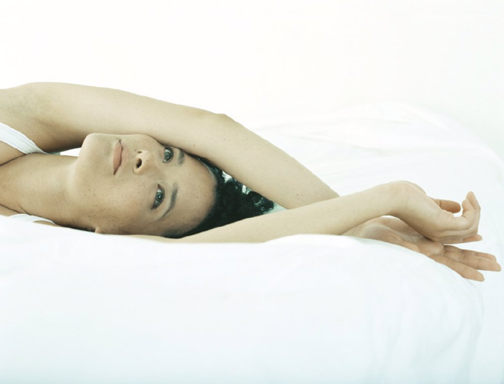 Woman lying on bed with arms crossed at wrists above head : Stock Photo