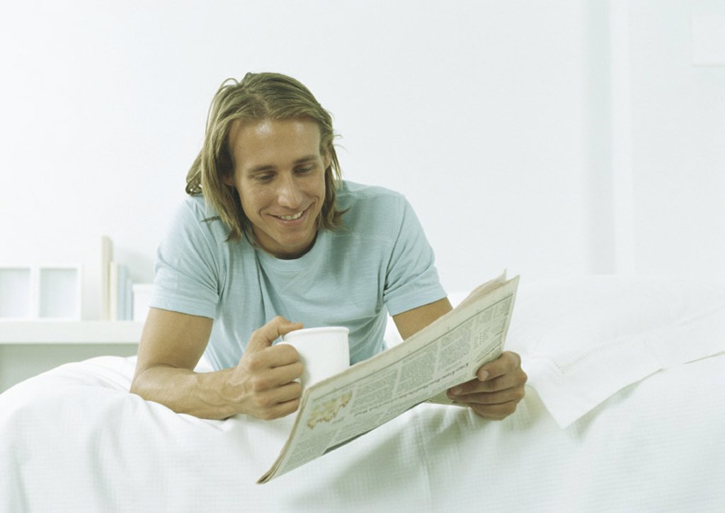 Young man lying on stomach with mug in one hand and newspaper in other : Stock Photo