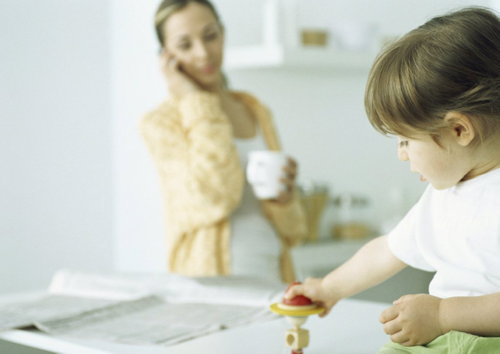 Little girl playing with toy, woman holding mug and talking on phone in background : Stock Photo