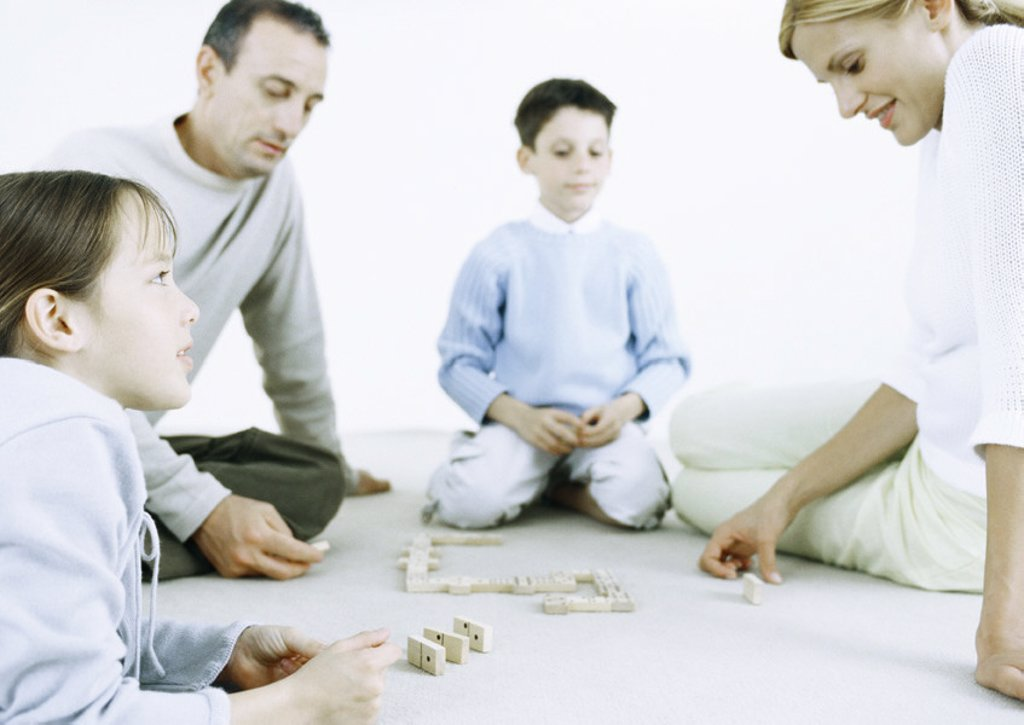 Girl and boy with parents playing dominoes on floor : Stock Photo