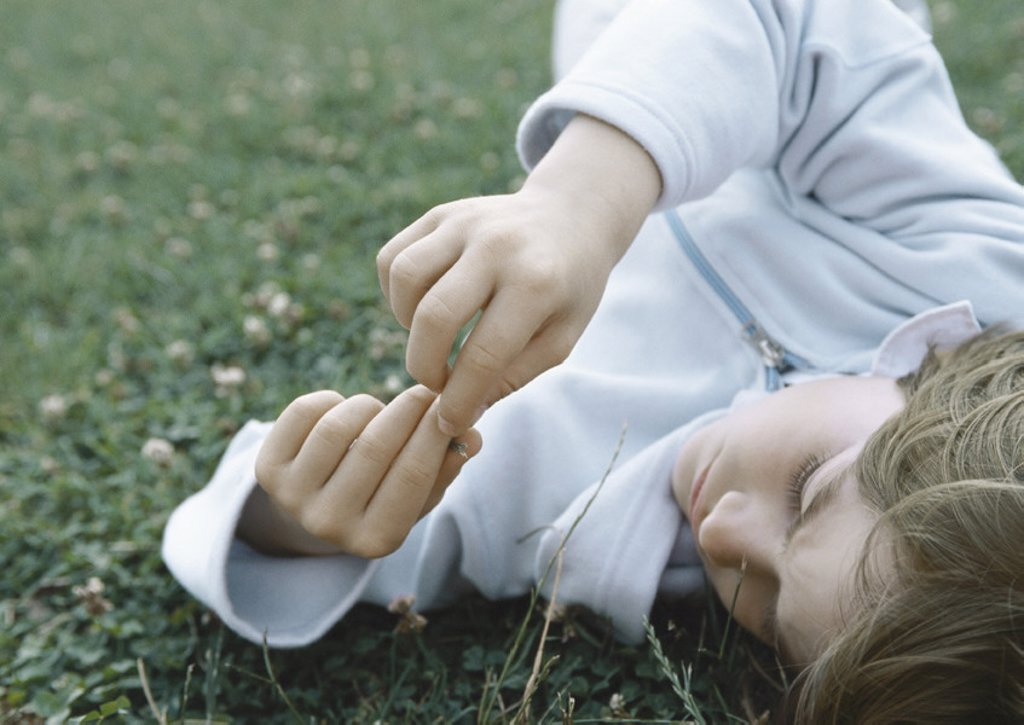 Boy lying on grass holding fingers together in front of face : Stock Photo