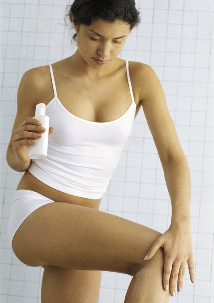 Stock Photo: 1569R-268034 Young woman standing in underclothes applying lotion to leg