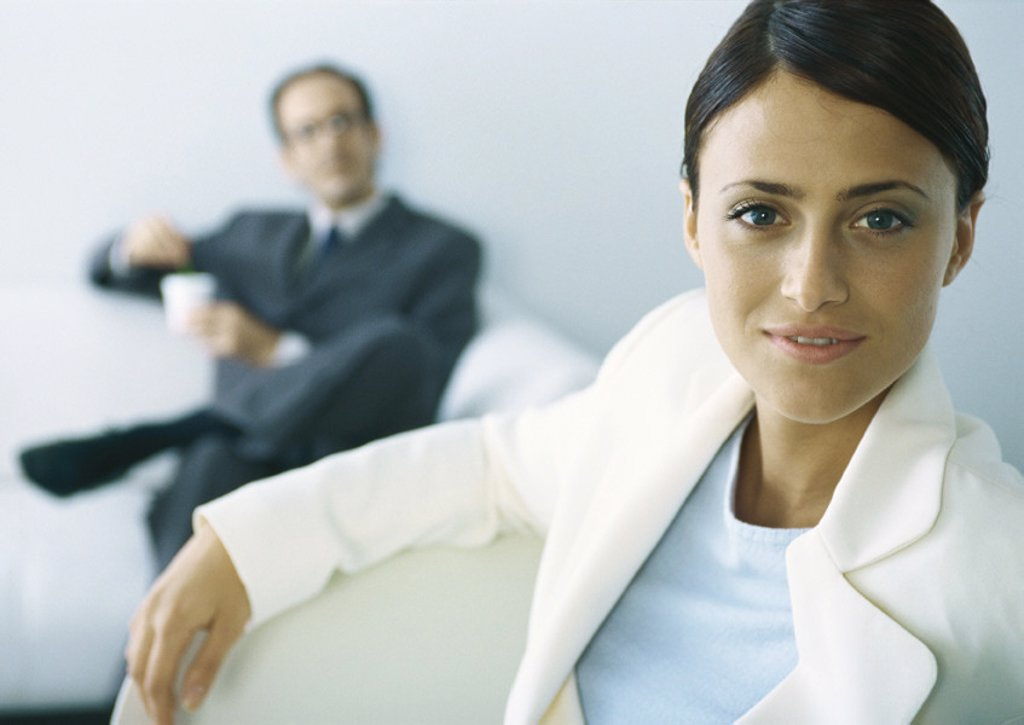Businesswoman looking at camera, businessman with legs crosses holding cup in background : Stock Photo