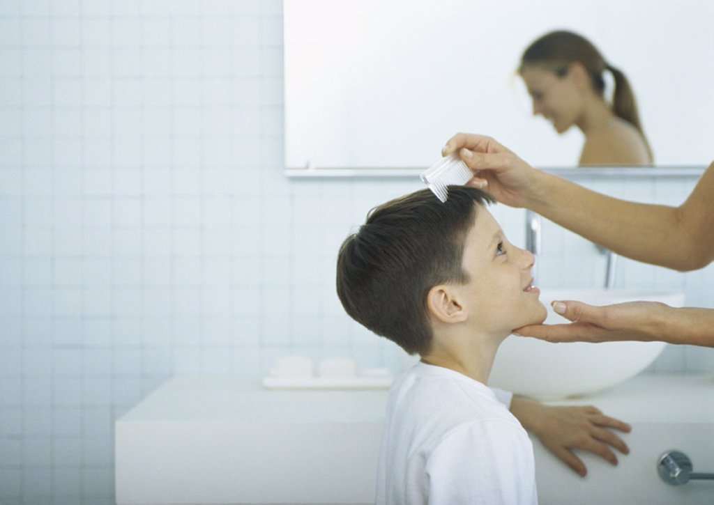 Woman combing boy´s hair : Stock Photo