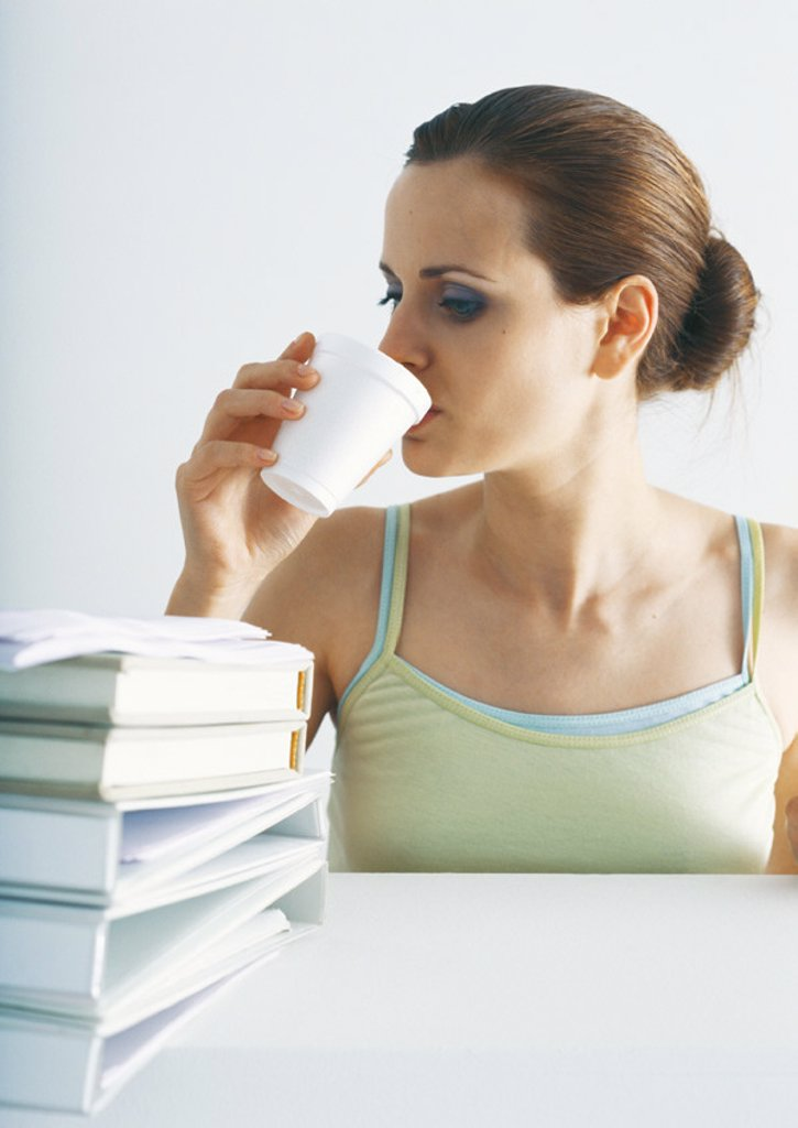 Stock Photo: 1569R-274031 Woman drinking at table with stack of folders