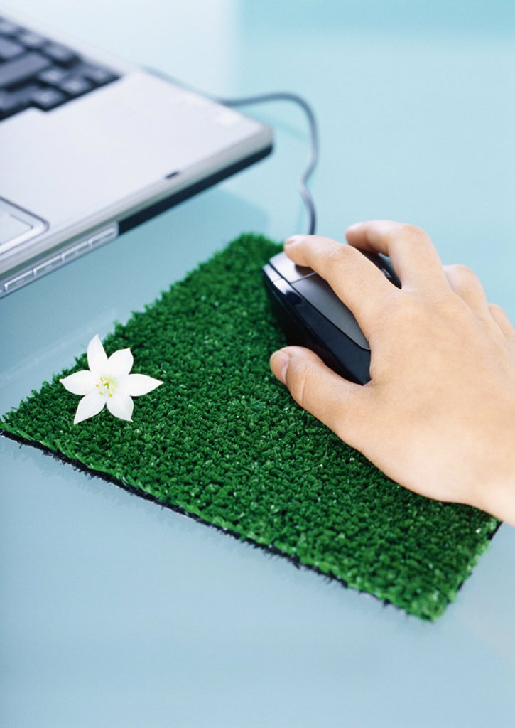 Hand using mouse on mouse pad made of artificial turf : Stock Photo