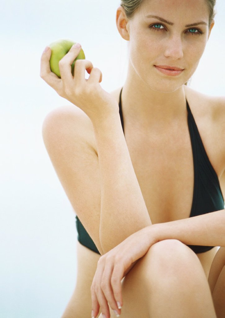 Young woman in bikini holding apple, looking at camera : Stock Photo