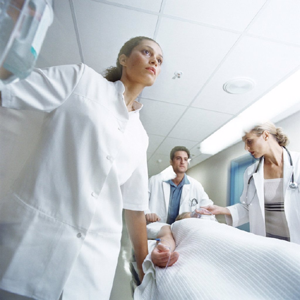 Medical team pushing patient on gurney : Stock Photo