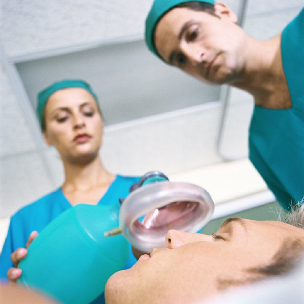Stock Photo: 1569R-290017 Doctors placing oxygen mask over patient´s face