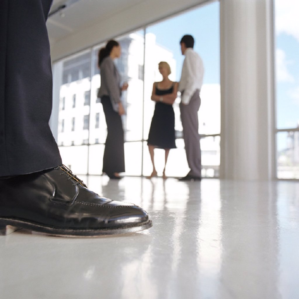 Stock Photo: 1569R-291049 Well-dressed man´s leg, well-dressed group standing near window