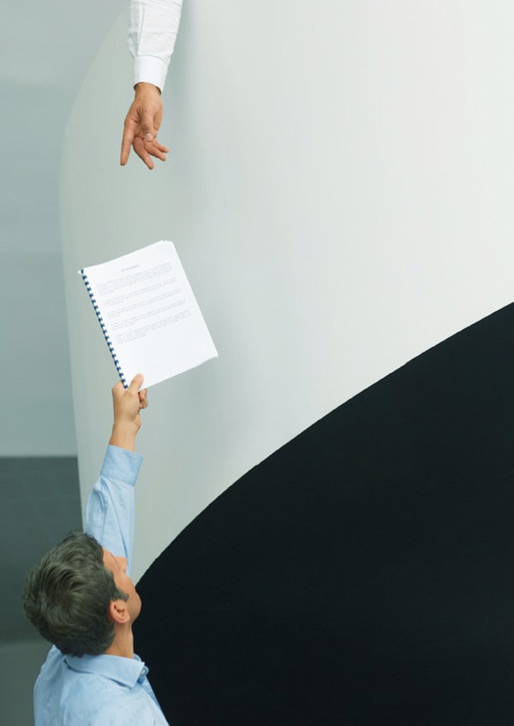 Man holding up document for second person reaching down : Stock Photo