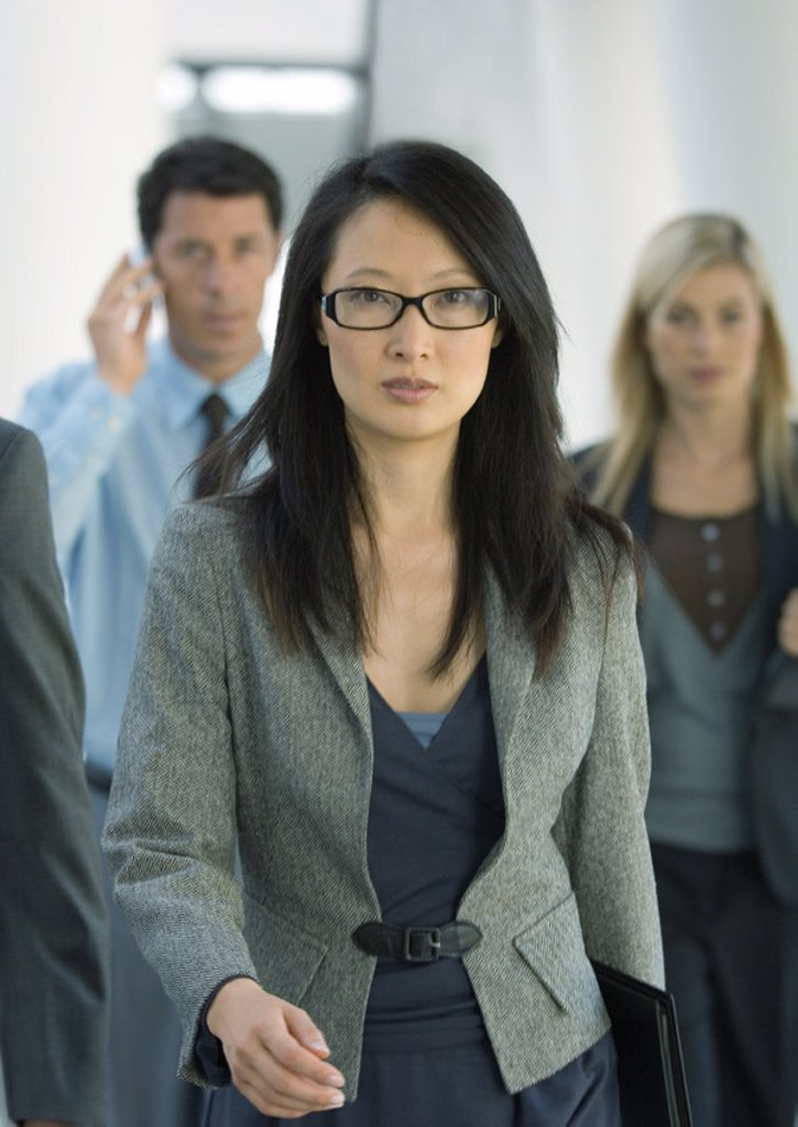 Businesswoman walking, colleagues behind her : Stock Photo
