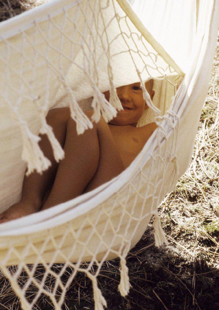 Child lying in hammock, smiling : Stock Photo