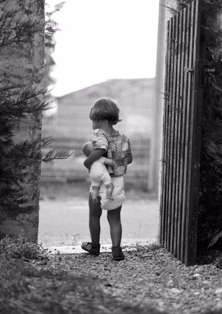 Stock Photo: 1569R-32108 Little girl holding baby doll in gateway, rear view, b&w