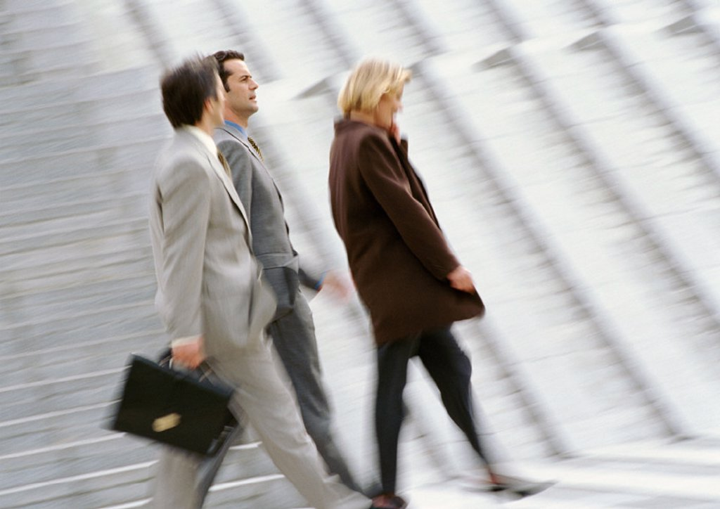 Three business people walking, blurred : Stock Photo