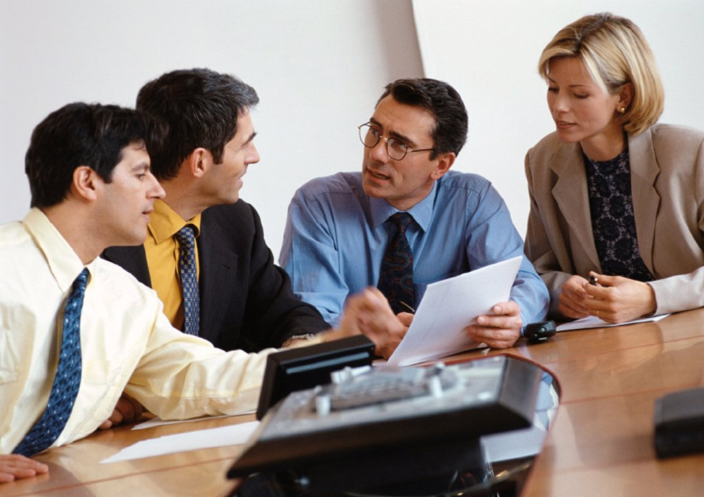 Three businessmen and a businesswoman examining document : Stock Photo