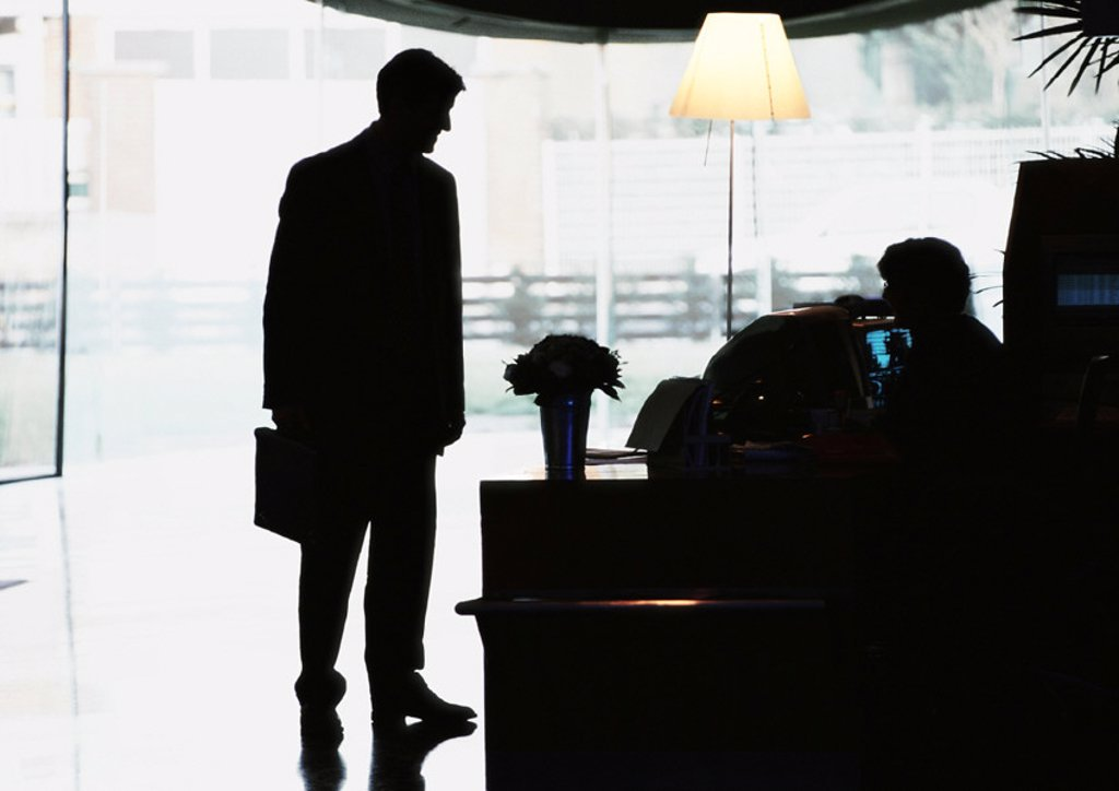 Silhouette of businessman standing by desk : Stock Photo