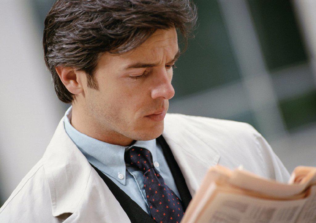 Stock Photo: 1569R-41058 Businessman reading newspaper, portrait