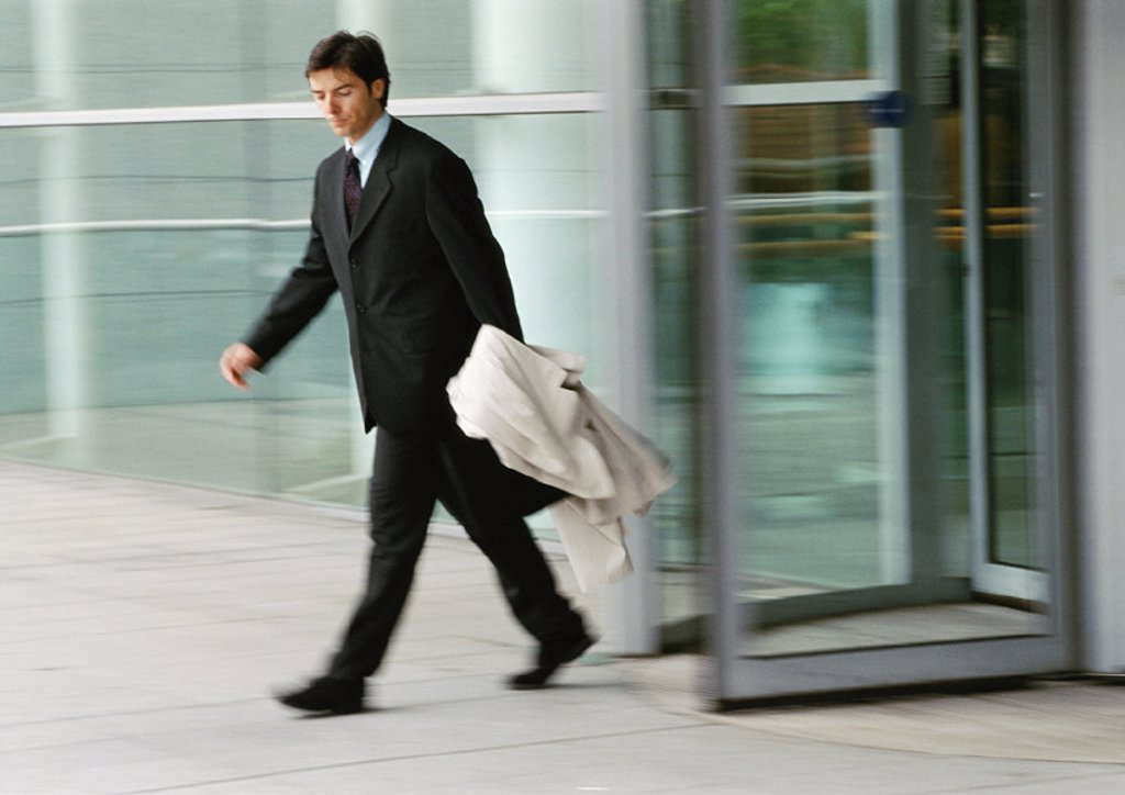 Businessman leaving building, holding overcoat, blurred : Stock Photo
