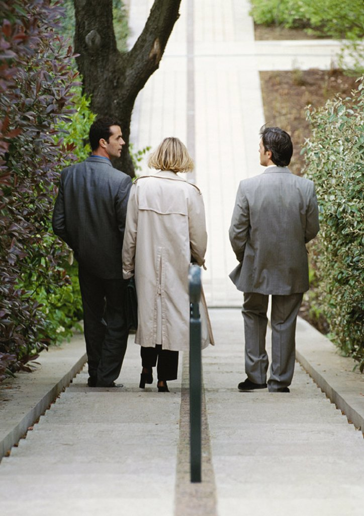 Three business people going down stairs, rear view : Stock Photo